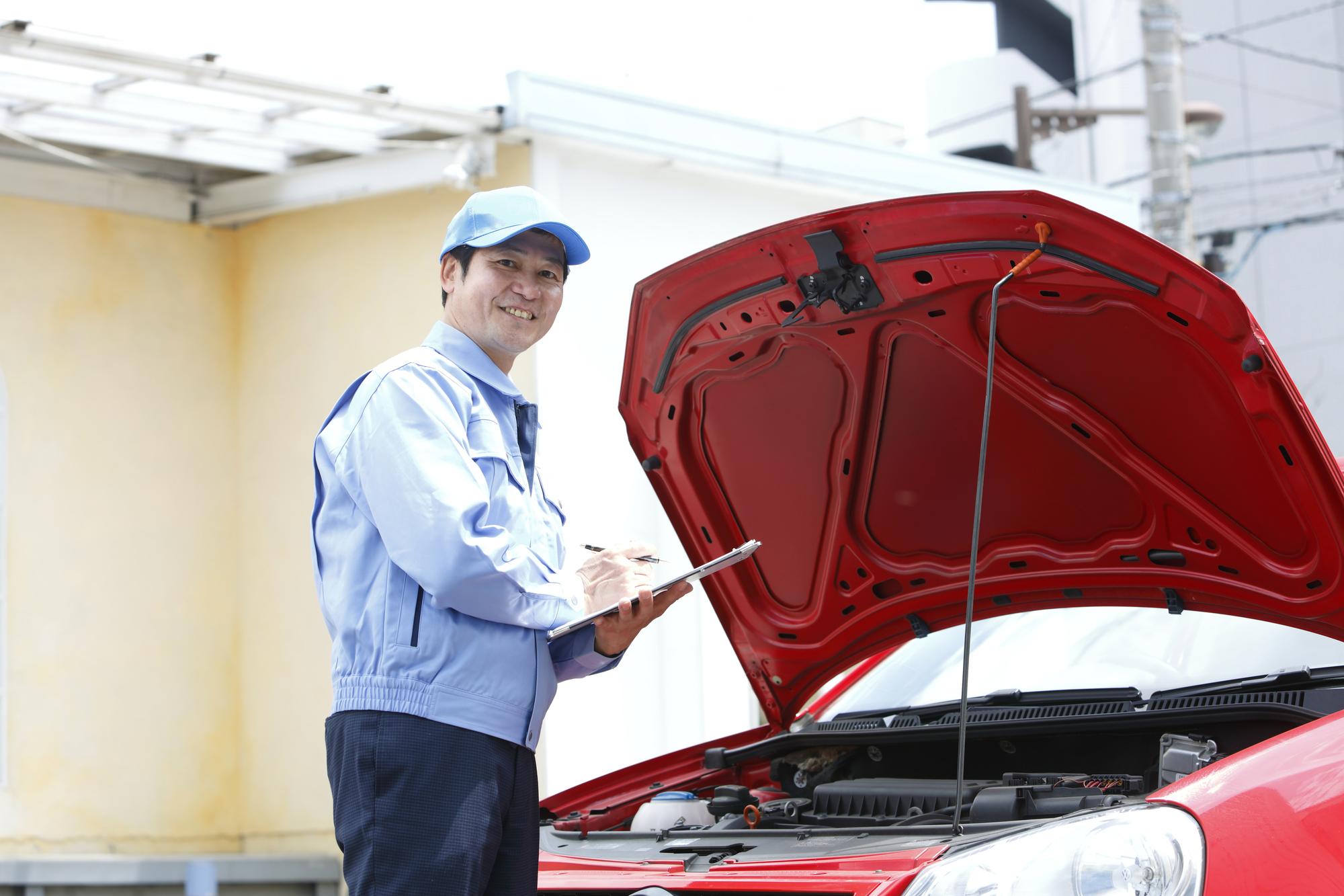 赤い車のボンネットを開けて検査する男性