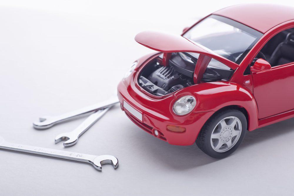 ボンネットを開けて修理をする赤い車